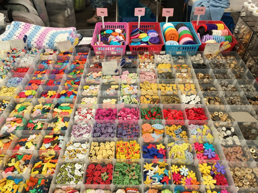 Trays of brightly coloured buttons on sale at Leicester Market